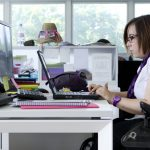 Young hip woman in a wheelchair at her desk with several computer open in front of her.