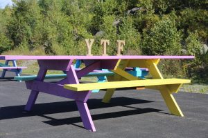 A Purple, Yellow and blue picnic table with the letters YTF on top.